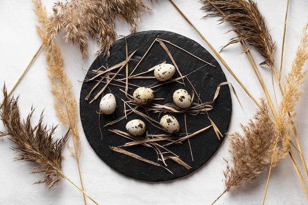 Плоская кладка пасхальных яиц на сланце с соломой и цветами