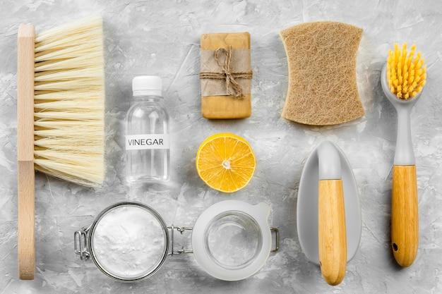 Плоский слой экологически чистых чистящих средств с кисточками и лимоном