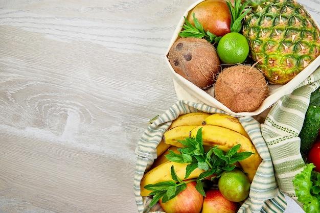 有機果物と野菜が入った環境にやさしい食料品の買い物用コットンバッグのフラットレイ