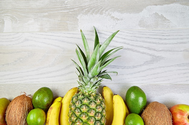 マンゴー、パイナップル、バナナ、アボカド、ココナッツ、ライムなど、白い背景にエキゾチックな果物の平らなレイアウト。上面図。トロピカル フルーツ、コピー スペース、夏のコンセプトで作られたクリエイティブ レイアウト。