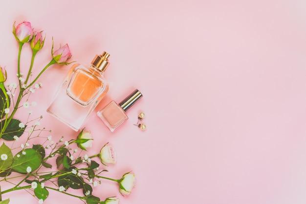 여성 화장품 제품 및 액세서리의 평평한 누워. 향수, 누드 매니큐어, 진주 earings 및 분홍색 배경에 장미의 병. 공간을 복사하십시오.