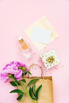 ピンクの背景の上に女性の化粧品、ギフトボックス、空のカードのフラットレイ。スペースをコピーします。