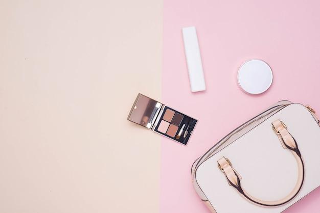 コピースペースとパステルカラーの背景に女性のファッションアクセサリーと白いハンドバッグのフラットレイ