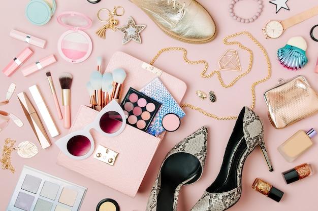 パステルカラーの背景に女性のファッションアクセサリー、メイクアップ製品、ハンドバッグのフラットレイ