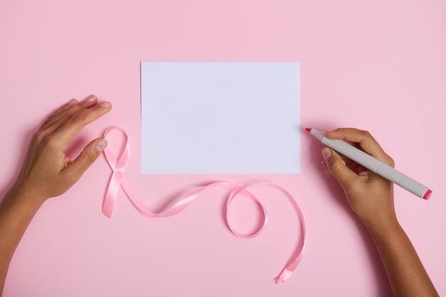 흰색 빈 종이에 쓸 준비가 된 펠트 펜을 들고 있는 평평한 여성 손, 10월 유방암 인식의 달의 분홍색 리본 기호, 텍스트를 위한 공간이 있는 분홍색 배경에 누워