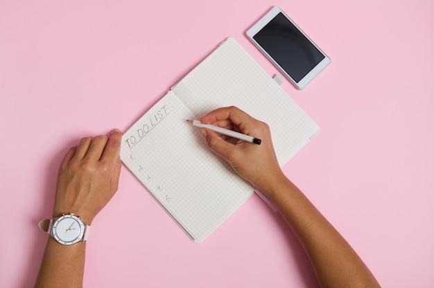 연필을 들고 공책에 글을 쓰고 할 일 목록을 확인하는 여성 손이 평평하게 놓여 있습니다. 텍스트에 대 한 공간을 가진 분홍색 배경에 누워 휴대 전화. 비즈니스, 계획 및 시간 관리 개념
