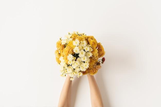 黄色と生姜を持っている女性の手の平らな横たわりは、白で隔離される野生の花の花束を落とします。上面図。 v
