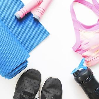 흰색 배경에 여성 스포츠 및 요가 장비의 평면 배치, 건강 개념의 상위 뷰