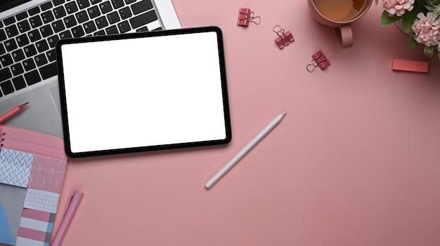 분홍색 테이블에 디지털 태블릿, 노트북, 문구류, 복사 공간이 있는 평평한 여성 작업 공간.