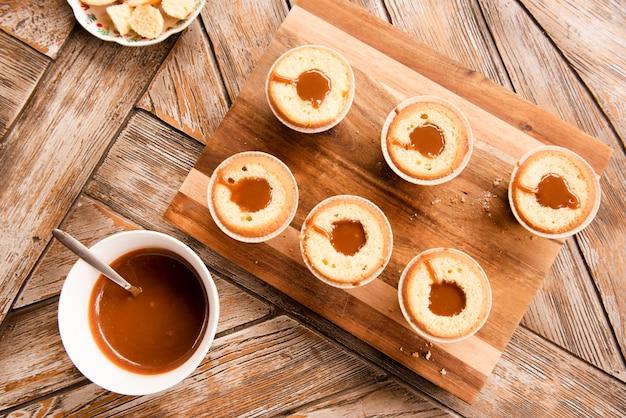 木製のテーブルにいっぱいのカップケーキのフラットレイアウト
