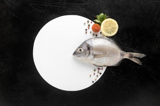 皿とレモンの魚のフラットレイアウト