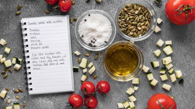 Плоская планировка пищевых ингредиентов с маслом и блокнотом