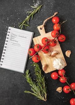 Плоская кладка пищевых ингредиентов с рецептом и помидорами