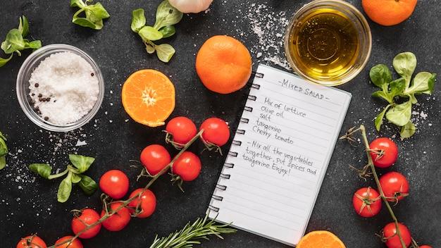 Плоская кладка пищевых ингредиентов с рецептом и овощами
