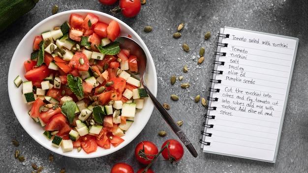 サラダとノート付きの食材のフラットレイ