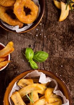 Плоский картофель фри в мисках с солью и зеленью