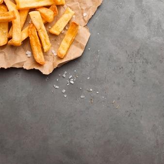 Плоская кладка картофеля фри на бумаге с солью и копией пространства