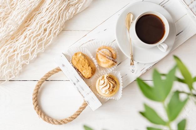 ブラックコーヒーとチョコレートフレンチデザートのフレッシュでリラックスした雰囲気のフラットレイ。きれいな白い背景のアフタヌーンティーアレンジメント