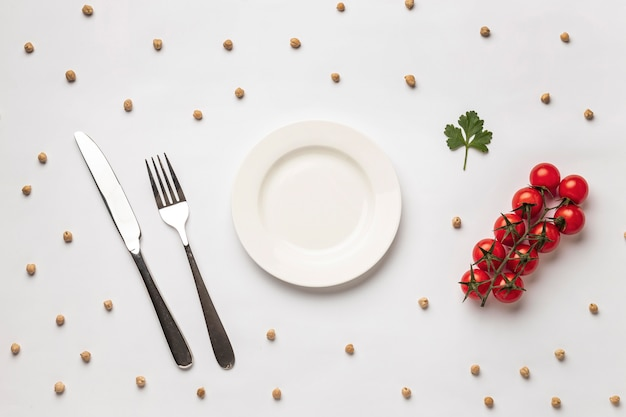 Плоская кладка свежих помидоров с тарелкой и столовыми приборами