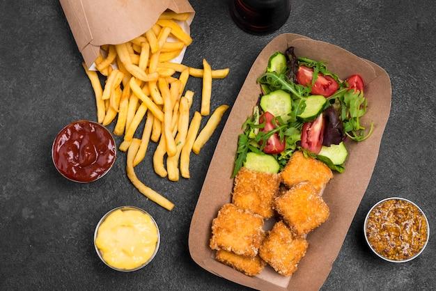 Плоская выкладка из жареных куриных наггетсов с салатом и картофелем фри