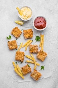 Плоская выкладка из жареных куриных наггетсов с соусами и картофелем фри
