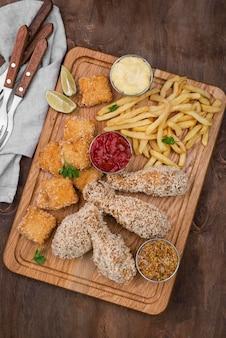 Плоская форма жареной курицы с картофелем фри и столовыми приборами