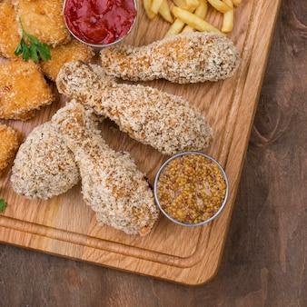 Плоская форма жареной курицы с соусом и картофелем фри