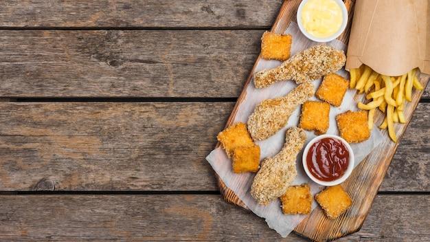 Плоская форма жареной курицы с соусами и картофелем фри