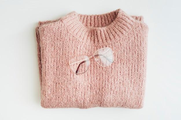 ピンクのニットセーターにメガネを平らに置く