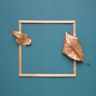Плоская планировка из золотых листьев и рамы на бирюзовом фоне с копией пространства. минималистичная концепция сбора урожая, осень