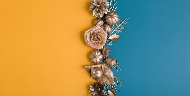 色の背景に金色のどんぐり、コーン、葉、カボチャのフラットレイ