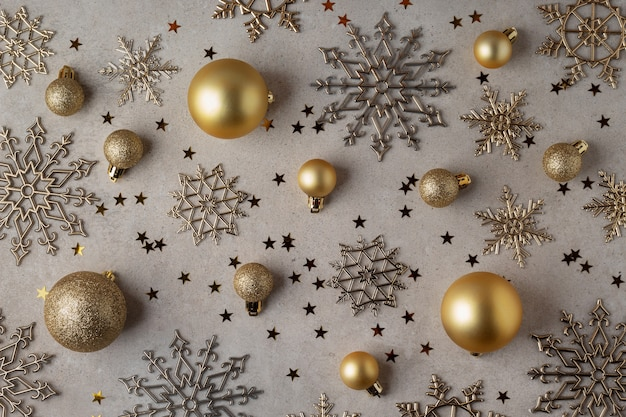 灰色の背景の上に金色のクリスマスボールと雪片のフラットレイ