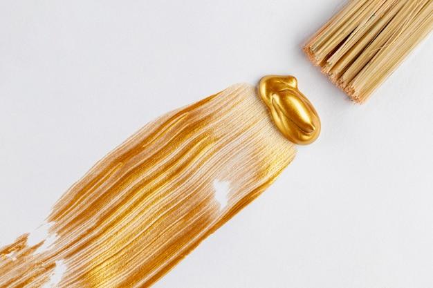 金色の塗料とブラシのフラットレイアウト