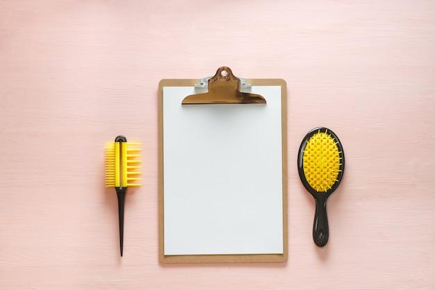 Плоская планировка расчесок для волос гребня с ручкой для всех типов, зеркальце и папка планшета, изолированные на розовом копией пространства. минималистичная женская плоская планировка для блогеров, дизайнеров, сайтов