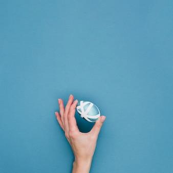 コピースペースでイースターの塗られた卵を持っている手のフラットレイアウト