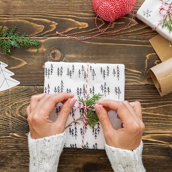 Плоское положение рук, связывающих рождественский подарок веревкой