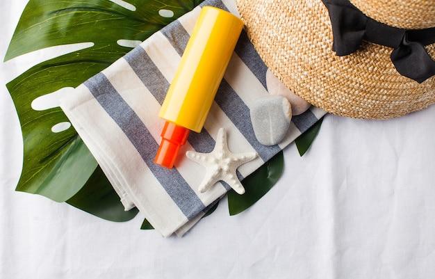 복사 공간 흰색 수건에 모자 조개 선크림의 평면 누워