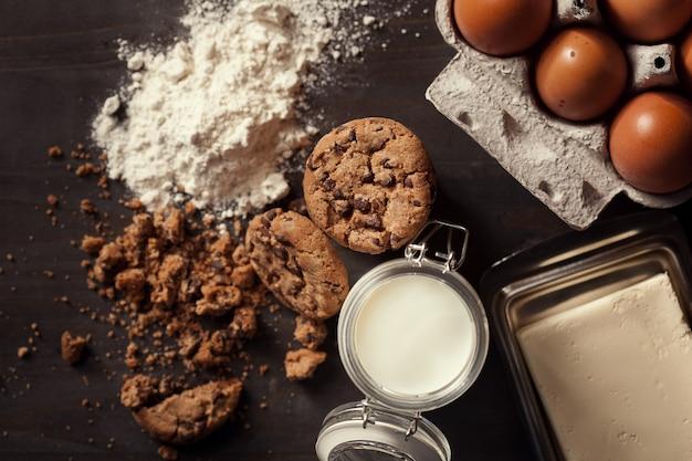 素朴な木製のテーブルにミルク、白い小麦粉、新鮮な卵、パン粉のボトルと自家製チョコレートチップクッキーのフラットレイ。美味しいおやつ。
