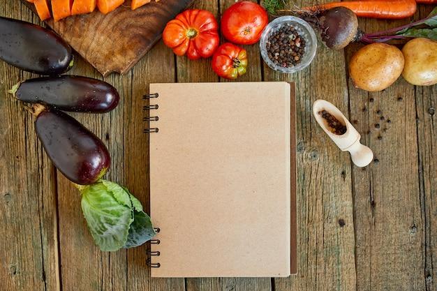 Плоская планировка ингредиентов для приготовления пищи, овощи вокруг книги рецептов