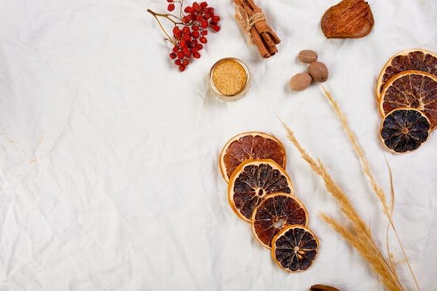 흰색 직물 린넨 식탁보, 정물, 천 질감 배경, 크리스마스 음료, 복사 공간에 겨울 계절 멀드 와인을 위한 평평한 재료와 레드 와인 한 병.