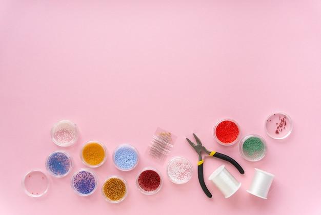 創造性のためのアイテムのフラットレイ。ピンクの背景、コピースペースのビーズ、釣り糸、ワイヤーカッター。