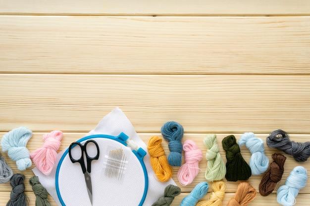 刺繡用のアイテムのフラットレイ。木製のフープ、フロス糸、針、帆布