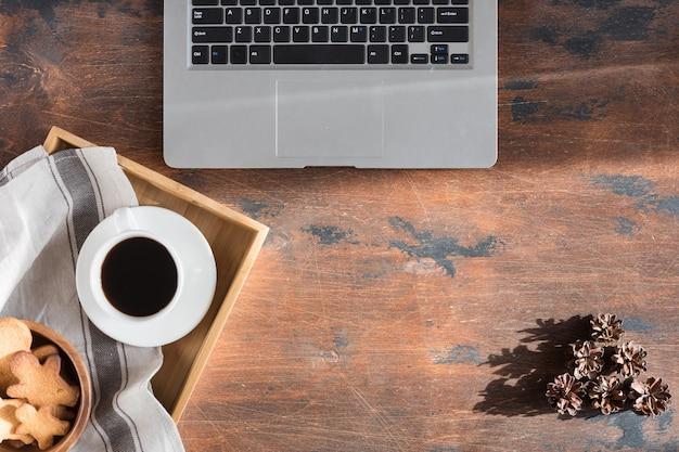 빈티지 나무 데스크탑에 평평한 노트북, 그림자가 있는 책상 위의 위쪽 전망, 단단한 빛.