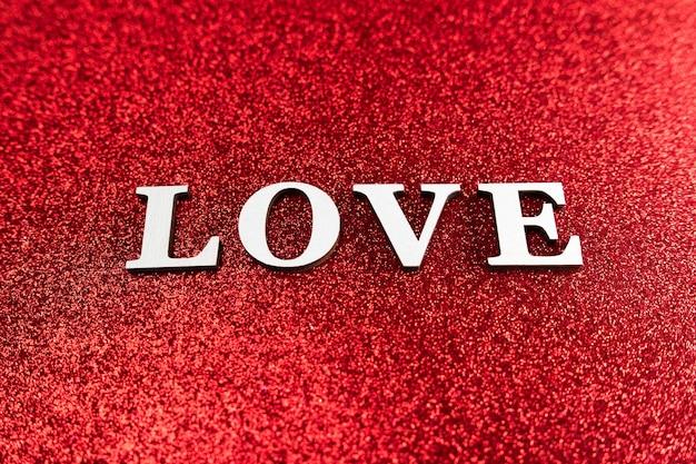 真っ赤なキラキラの輝きの背景に愛の概念のフラットレイ
