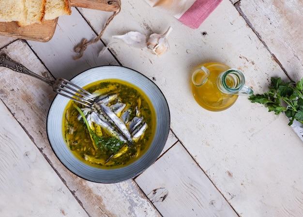 Плоский слой маринованных анчоусов в лимонном соке с оливковым маслом, чесноком и петрушкой. традиционная средиземноморская летняя еда
