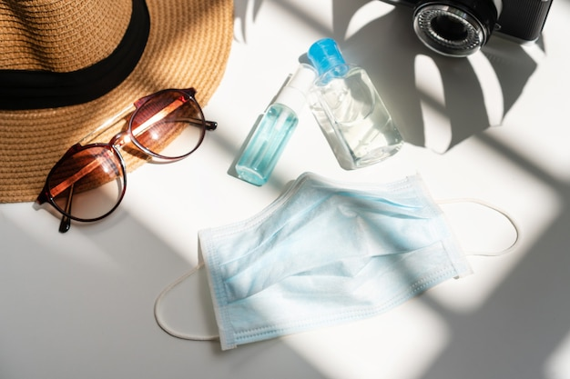 机の上にマスク、消毒ジェル、アルコールスプレーを平らに置きます。夏、休日、ヘルスケアの概念