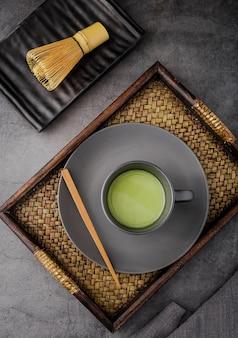Плоская укладка чайной чашки матча на подносе