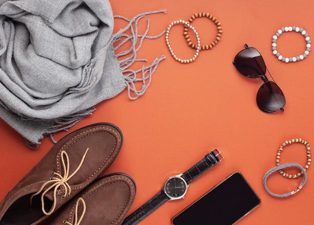 オレンジ色の背景の上の靴、時計、電話、イヤホン、サングラス、スカーフとメンズアクセサリーのフラットレイアウト