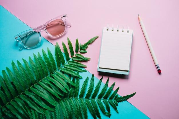 Плоская планировка минимального рабочего стола с блокнотом и зеленым растением