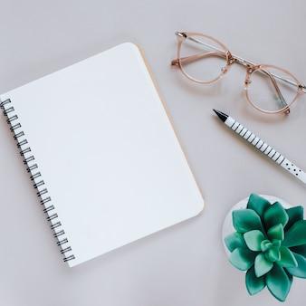 ノートブック、眼鏡および緑の植物、コピースペースを備えた最小限の作業スペースデスクの平らなレイアウト